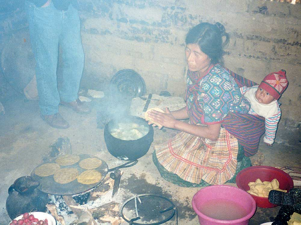 Woman in smoky cooking hut